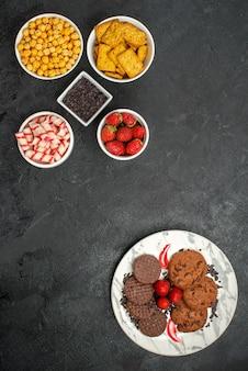 Vista de cima, biscoitos de chocolate saborosos com diferentes lanches no fundo escuro.