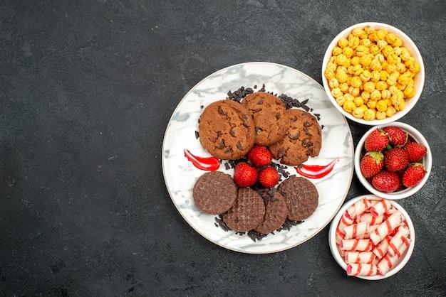 Vista de cima, biscoitos de chocolate saborosos com doces em fundo escuro, bolo de açúcar, biscoito doce
