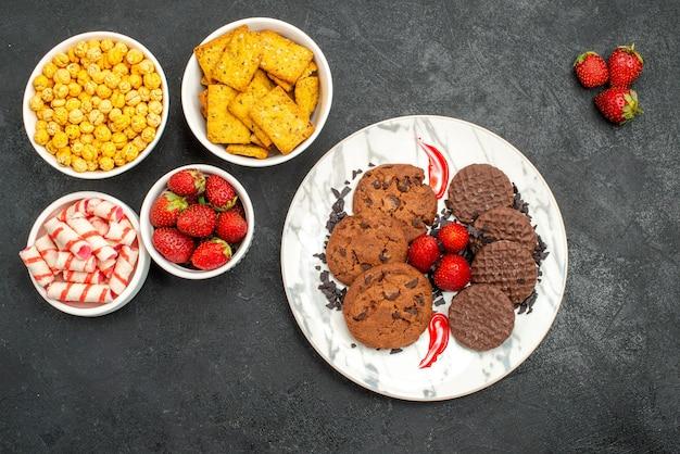 Vista de cima, biscoitos de chocolate saborosos com petiscos diferentes em fundo escuro, biscoitos doces de chá