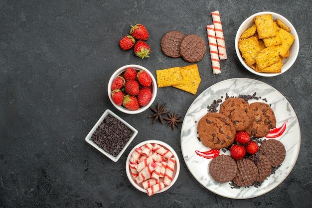 Vista de cima, biscoitos de chocolate saborosos com petiscos diferentes em fundo escuro chá de biscoitos doces