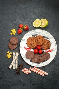 Vista de cima, biscoitos de chocolate saborosos para chá no fundo escuro biscoito doce chá de açúcar