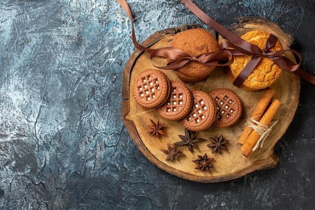 Vista de cima, biscoitos e biscoitos anis em pau de canela em uma placa de madeira redonda em uma mesa escura.