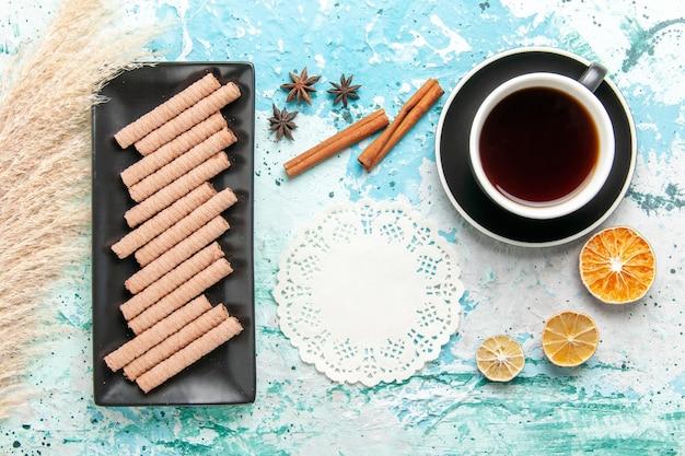 Vista de cima biscoitos longos doces com uma xícara de chá e canela no fundo azul