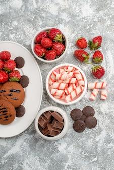 Vista de cima biscoitos, morangos e chocolates redondos no prato oval branco e tigelas de doces e morangos chocolates na mesa cinza-esbranquiçada