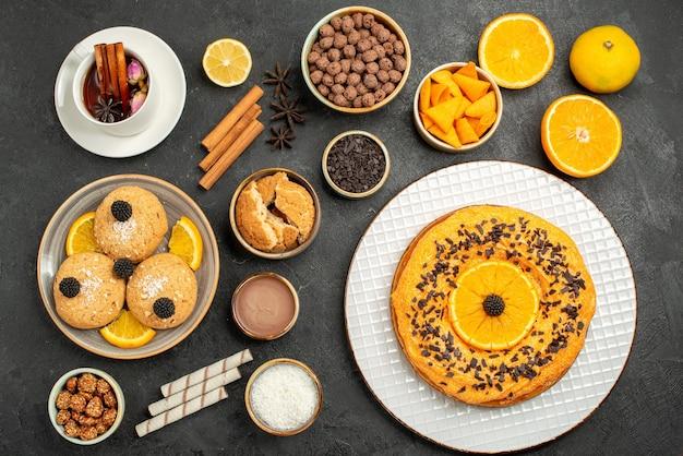 Vista de cima biscoitos saborosos com torta doce e xícara de chá na superfície escura torta de bolo açúcar sobremesa biscoito chá