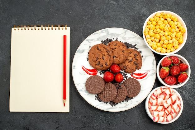Vista de cima, biscoitos saborosos de chocolate com doces em fundo escuro