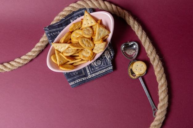 Vista de cima biscoitos salgados dentro de um prato rosa com cordas no fundo rosa, biscoito crocante lanche cor de comida