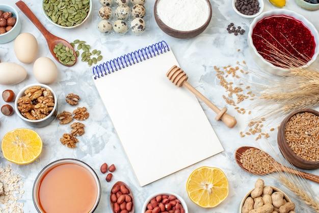 Vista de cima, bloco de notas aberto com ovos, farinha, geleia, diferentes nozes e sementes em uma massa de noz branca, bolo, torta doce, foto açúcar