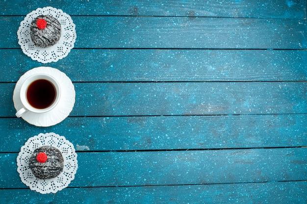 Vista de cima, bolas de chocolate saborosas com uma xícara de chá na mesa rústica azul, bolo de chá, biscoitos, biscoito, doce