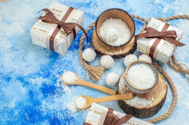 Vista de cima, bolas de coco, tigelas de corda com pó de coco no fundo branco azul