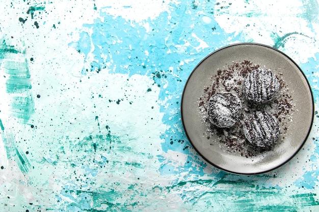 Vista de cima, bolinhas de chocolate deliciosas, bolos de chocolate redondos formados com glacê na mesa azul