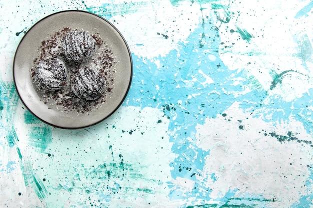 Vista de cima, bolinhas de chocolate deliciosas, bolos de chocolate redondos formados com glacê na superfície azul