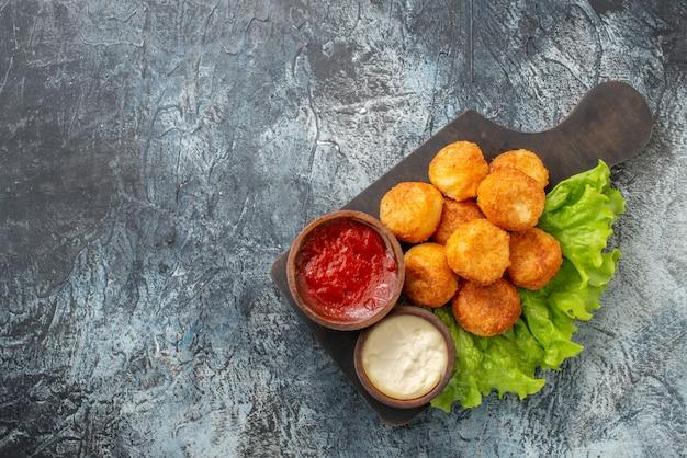 Vista de cima, bolinhas de queijo frito, tigelas de molho de alface na tábua de cortar no espaço livre da mesa cinza