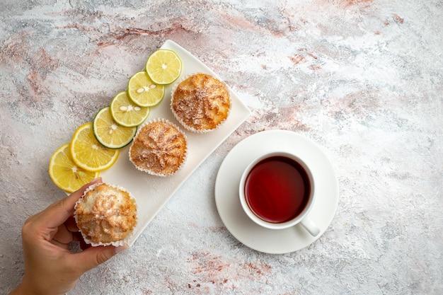 Vista de cima bolinhos assados e com rodelas de limão e uma xícara de chá na superfície branca