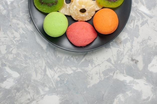 Vista de cima bolinhos coloridos com anéis de abacaxi secos na superfície branca