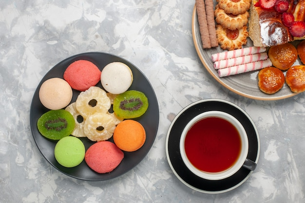 Vista de cima bolinhos coloridos com uma xícara de biscoitos de chá e bolo de morango em uma superfície branca