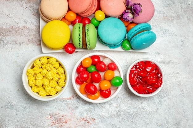 Vista de cima bolinhos coloridos deliciosos macarons com doces no espaço em branco