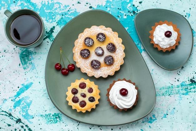 Vista de cima bolinhos com açúcar em pó creme de frutas na mesa azul claro bolo de frutas chá doce