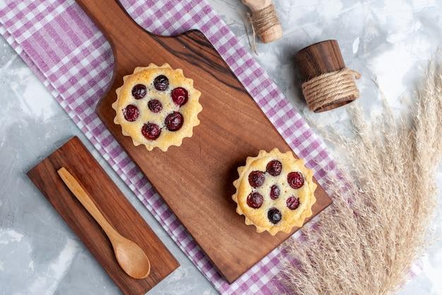 Vista de cima bolinhos com açúcar em pó e frutas na mesa clara bolo creme frutas chá doce