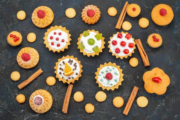 Vista de cima bolinhos com creme junto com biscoitos e canela na superfície escura.