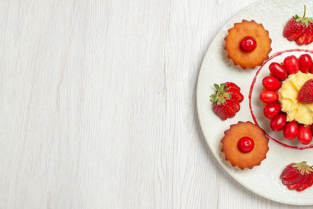 Vista de cima bolinhos com frutas dentro de um prato na mesa branca