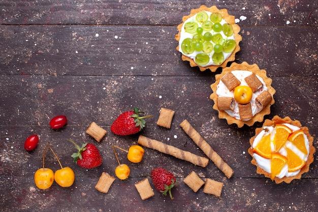 Vista de cima bolinhos cremosos com fatias de uvas, laranjas e morangos na mesa de madeira marrom.