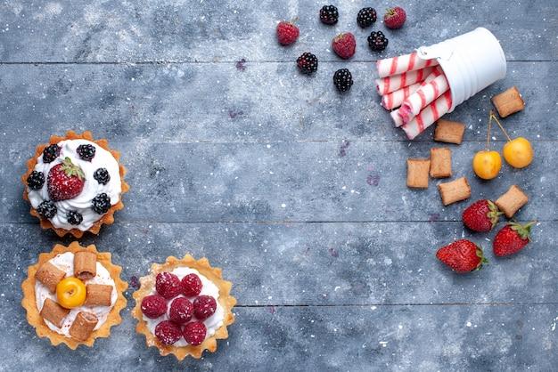 Vista de cima bolinhos cremosos com frutas vermelhas junto com biscoitos de morango e doces em palito rosa na mesa brilhante.