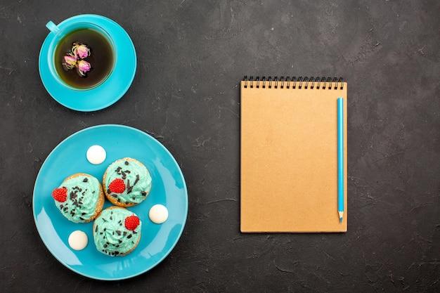 Vista de cima bolinhos cremosos, doces deliciosos com xícara de chá na mesa cinza-escuro, creme de chá, bolo, biscoito, cor de sobremesa