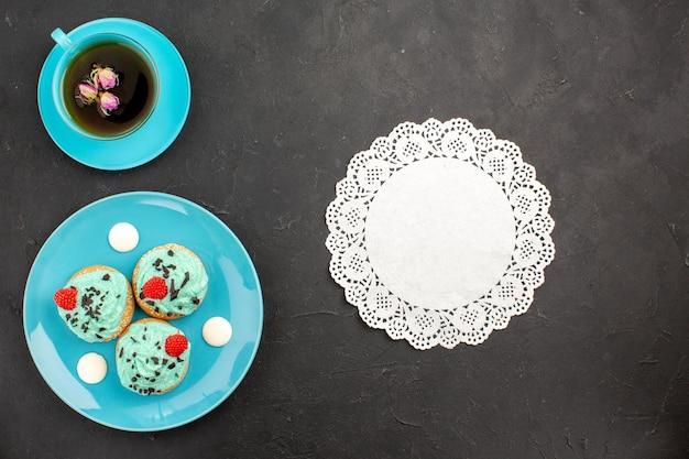 Vista de cima bolinhos cremosos, doces deliciosos com xícara de chá na superfície escura, creme de chá, bolo, biscoito, cor de sobremesa