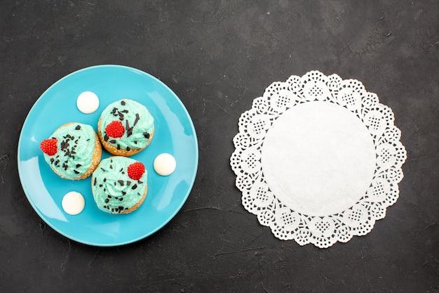 Vista de cima bolinhos cremosos doces deliciosos para chá dentro do prato na superfície cinza-escuro chá creme bolo biscoito cor sobremesa