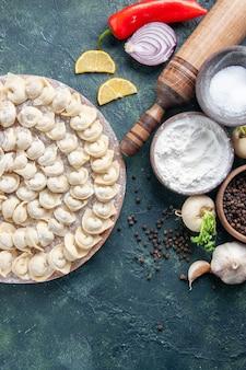 Vista de cima bolinhos de massa crus com farinha e vegetais em fundo escuro massa de carne comida cor caloria refeição de vegetais