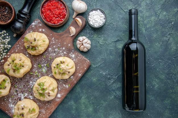 Vista de cima bolinhos de massa crus com molho de tomate em fundo azul escuro cozinhando massa de jantar prato refeição cozinha carne vinho