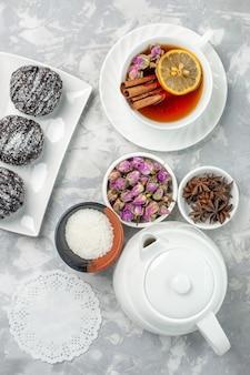 Vista de cima bolinhos deliciosos, bolos de chocolate com uma xícara de chá no fundo branco claro