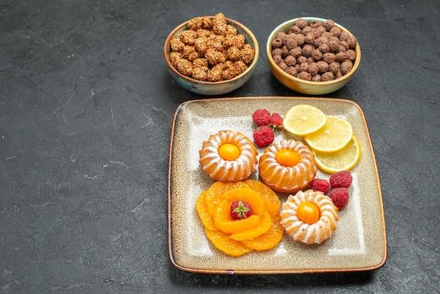 Vista de cima, bolinhos deliciosos com rodelas de limão, tangerinas e doces no espaço cinza