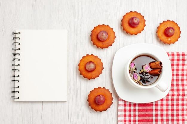 Vista de cima bolinhos deliciosos com uma xícara de chá na superfície branca frutas chá sobremesa biscoitos bolachas torta de bolo