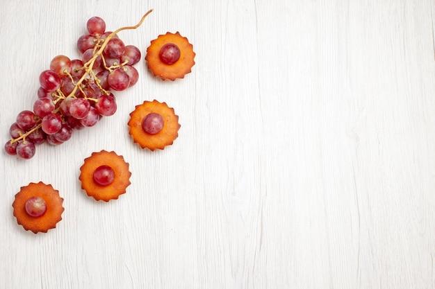 Vista de cima, bolinhos deliciosos com uvas frescas na superfície branca, sobremesa, biscoito, biscoito, chá, bolo, torta
