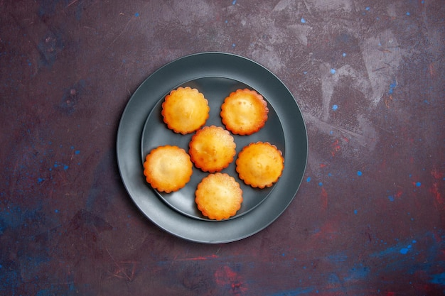 Vista de cima bolinhos deliciosos dentro do prato na superfície escura torta bolo de biscoito chá doce biscoito de açúcar