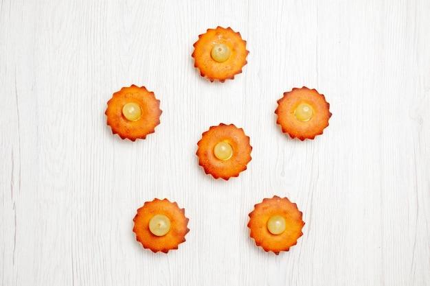 Vista de cima bolinhos deliciosos doces perfeitos para chá forrados em uma mesa branca torta de bolo doce sobremesa biscoitos de chá