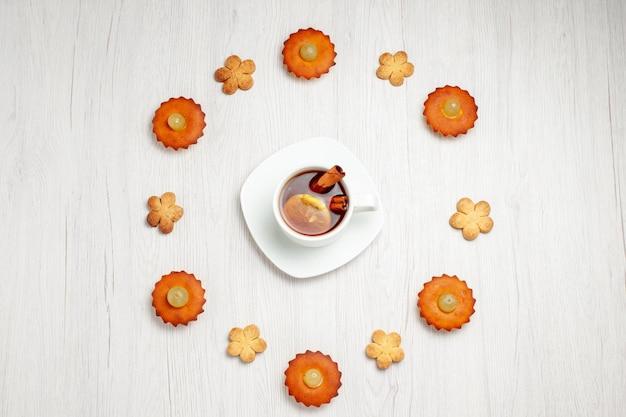 Vista de cima bolinhos deliciosos forrados com biscoitos e uma xícara de chá na superfície branca