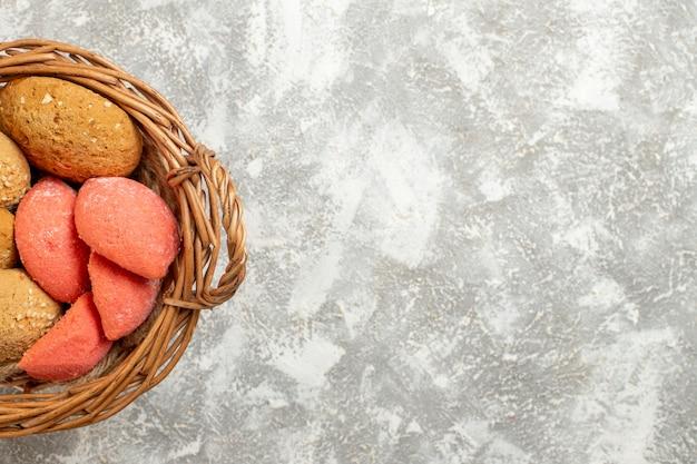 Vista de cima bolinhos doces dentro da cesta em fundo branco claro