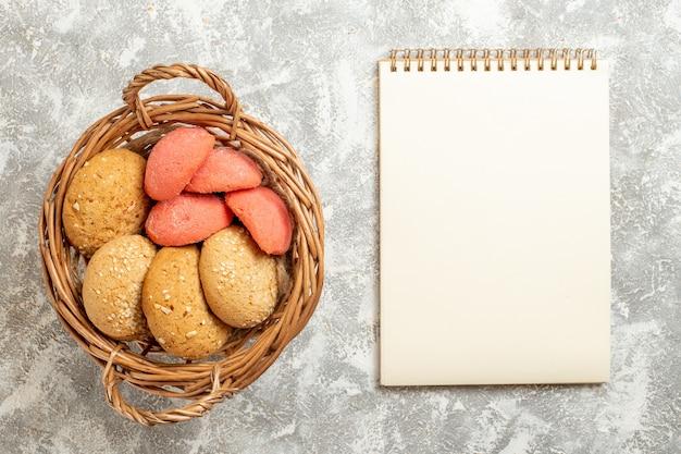 Vista de cima bolinhos doces dentro da cesta em fundo branco