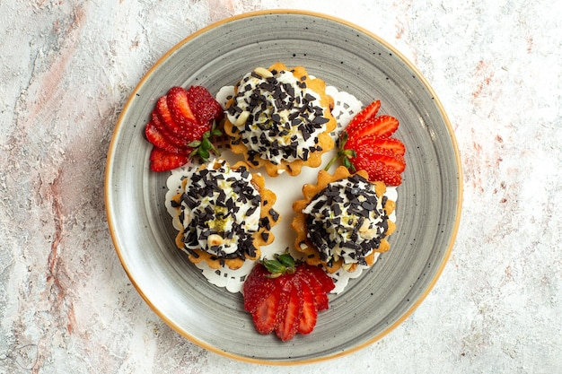 Vista de cima bolinhos gostosos com creme e morangos na superfície branca