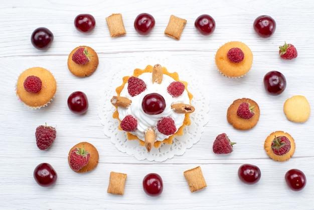 Vista de cima bolinhos gostosos com framboesas e creme junto com biscoitos e bolos na mesa leve bolo biscoito doce baga assar frutas