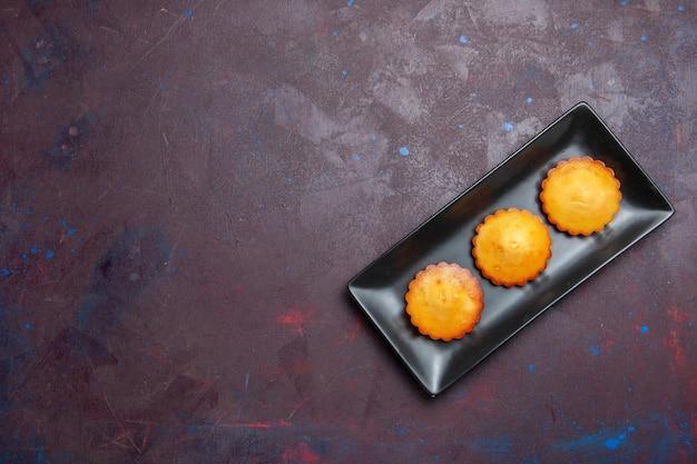 Vista de cima bolinhos gostosos dentro de uma fôrma preta na superfície escura torta biscoito biscoito doce chá bolo