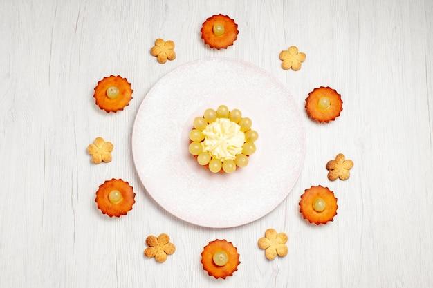 Vista de cima bolinhos gostosos forrados em uma mesa branca, sobremesa, biscoito, chá, bolo, torta, biscoito doce