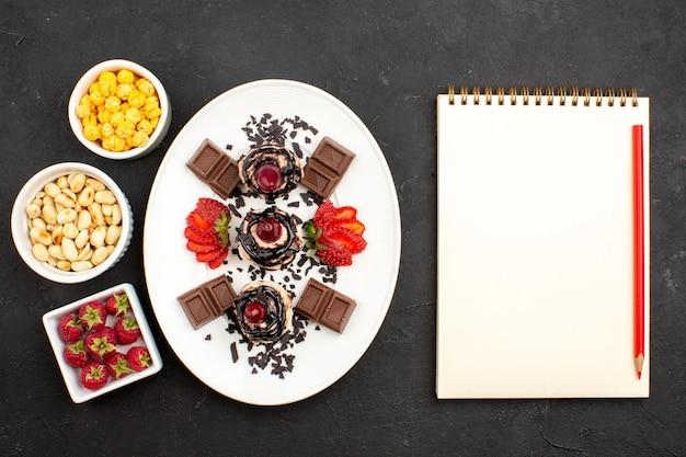Vista de cima bolinhos saborosos com barras de chocolate e nozes na superfície escura