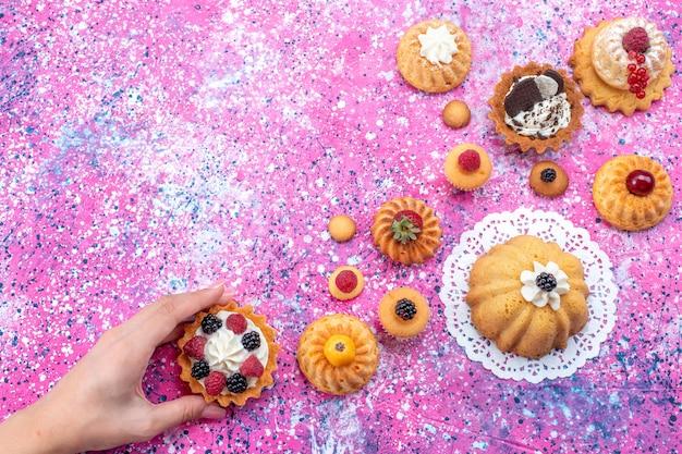 Vista de cima bolinhos saborosos com creme junto com diferentes frutas silvestres no fundo claro e brilhante bolo biscoito baga doce assar