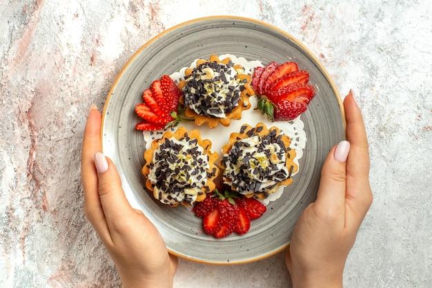 Vista de cima bolinhos saborosos com morangos na superfície branca bolo de biscoito doce comemoração de aniversário