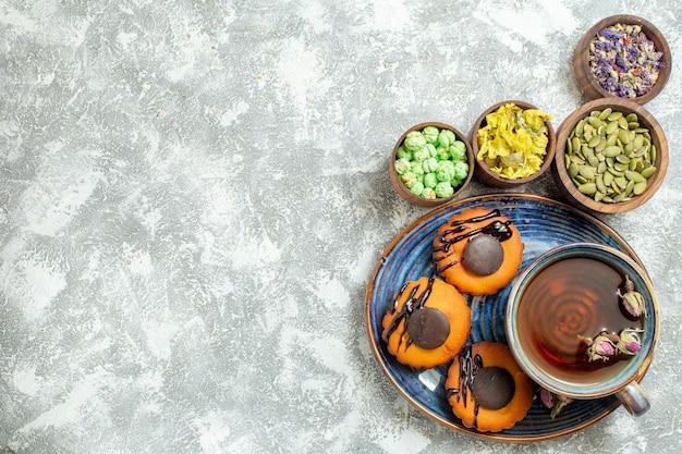 Vista de cima bolinhos saborosos com uma xícara de chá na superfície branca bolo biscoito biscoito sobremesa doce chá