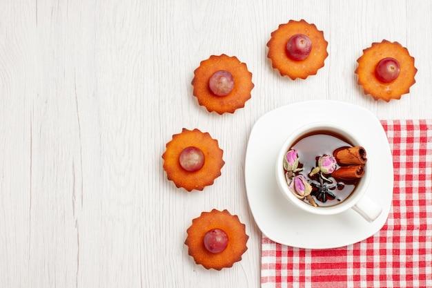 Vista de cima bolinhos saborosos com uma xícara de chá na superfície branca frutas chá sobremesa bolacha torta de bolacha